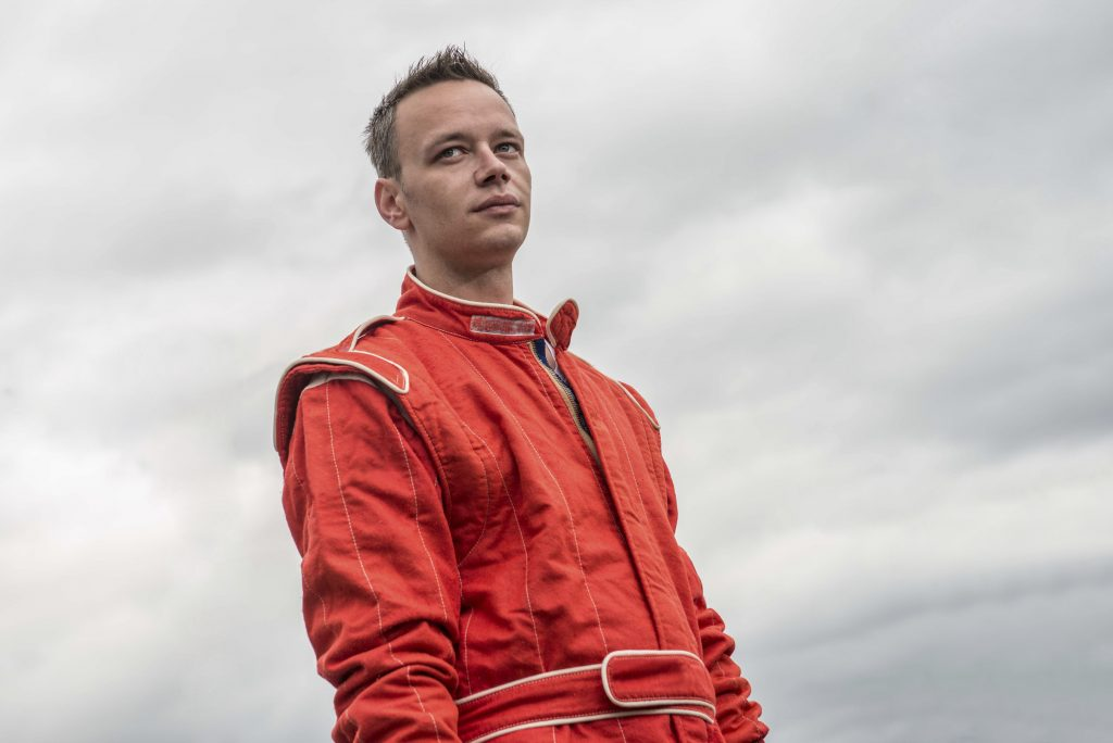 Formula 1 pilot in red racing protective suit. Outdoor. Sky background.Series